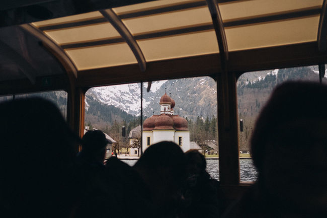 View of chapel St. Bartholomä from a boat on Königssee, Bavaria, Germany. Bavaria Horizontal Schönau Am Königsee Travel Photography Winter Alps Beauty In Nature Boat Close-up Day Domestic Animals Europe Friendship Germany Indoors  Königsee Lake Landmark Leisure Activity Lifestyles Looking Through Window Mammal Men Mountain Nature One Animal One Person Pets Real People Rear View Silhouette Sitting Sky Vacations Vehicle Seat Window Women