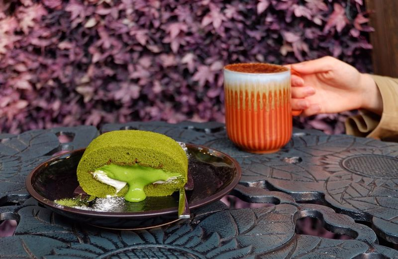 Matcha roll cake on ceramic plate on table with woman hand hold coffee latte cup,purple leaf for background Vintage Coffe Shop Garden Party Sweet Dessert Drink Leaf Shop Beverage Cream Cup Afternoon Tea Whipped Cream Coffee Latte Lifestyles Lifestyle Luxury Urban Cafe Cake Matcha Green Tea Human Hand Hand Food And Drink Holding Table Drink