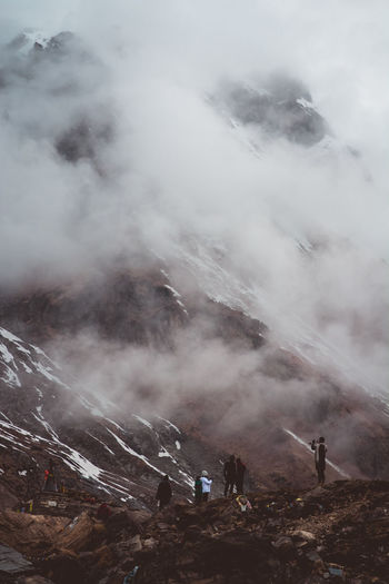 Group of people on mountain during foggy weather
