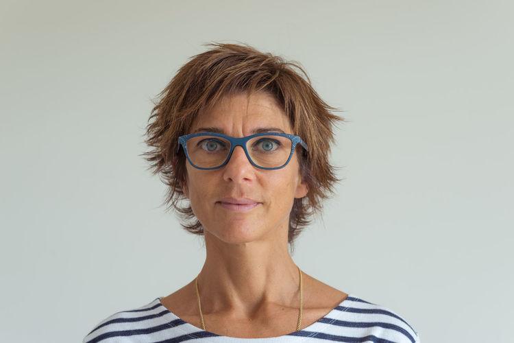 Portrait Of Woman Wearing Eyeglasses Against Gray Background