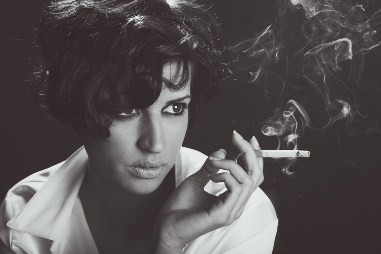 Young Woman Smoking Cigarette Against Black Background