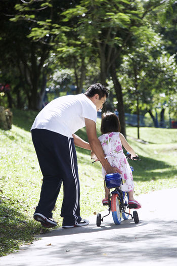 Father Teaching Bicycle To Daughter In Park