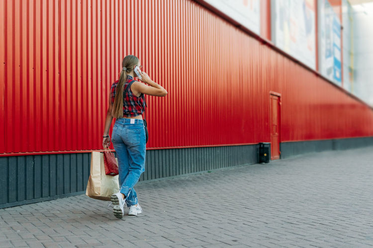 Full length of woman standing on footpath