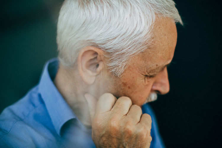 senior man looking away from camera Loneliness Aging Aging Beauty Aging Process Close-up Day Gray Hair Headshot Indoors  Lifestyles Men One Person One Senior Man Only People Real People Sad Sad & Lonely Sadness Senior Adult Senior Men Studio Shot