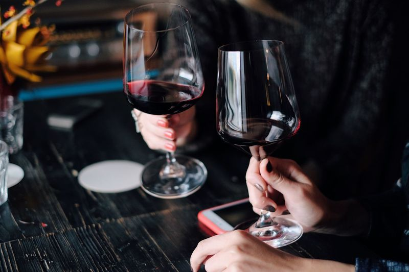 Woman's holding glass with red wine Wineglass Red Wine Wine Human Hand Human Body Part Indoors  Refreshment Food And Drink Real People Table Drink Two People Alcohol Close-up Wine Tasting Red Wine Mobile Phone Autumn Beverages Helloween Copy Space Food And Drink