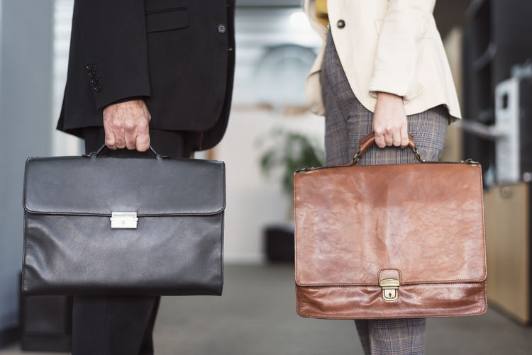 Midsection of colleagues holding briefcase while standing in office