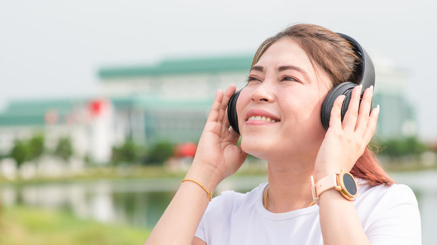 Portrait of smiling woman using mobile phone outdoors