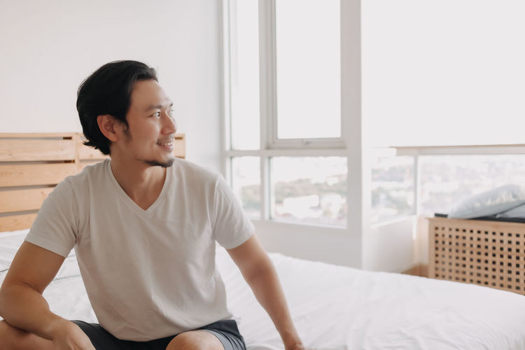 Young man looking away while sitting on bed