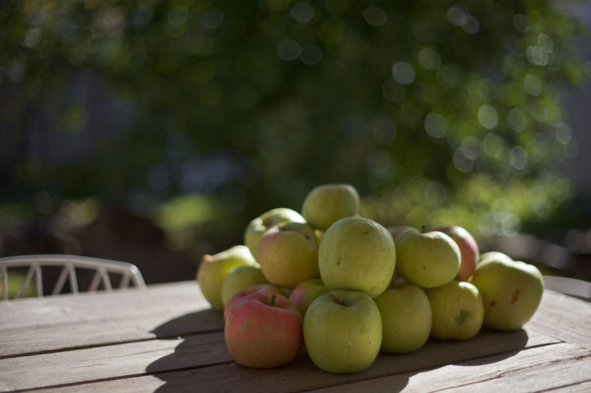 Autumn Autumn colors Green Apples  Apples Backlit Close-up Day Focus On Foreground Food Food And Drink Fresh Fruit Freshness Fruit Green Color Green Fruit Healthy Eating Nature No People Outdoors Red Apples rule of thirds Table Tree Wood - Material