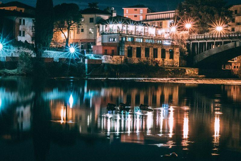 Illuminated buildings by lake at night