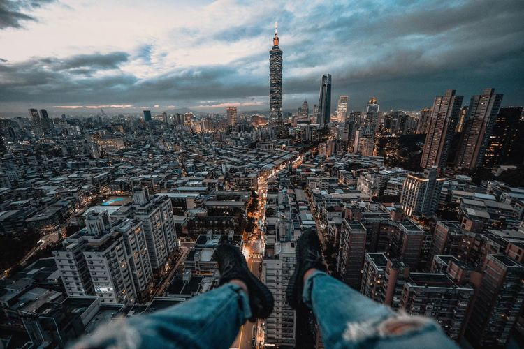 Low section of person over cityscape against sky