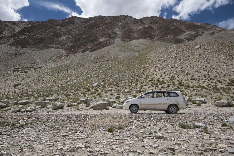 Car on desert against sky