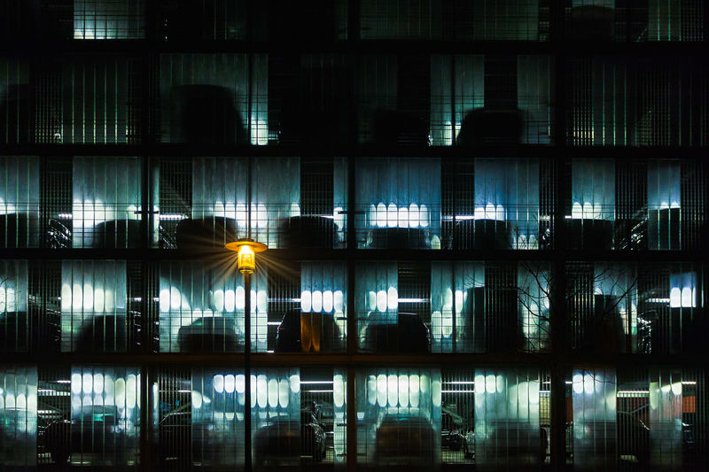 Multi-storey car park by night Dark Cars Shelf Multi-storey Multi-storey Car Park Car Park Electric Lamp Light Glowing Pattern Outdoors Transparent Modern City Window Glass - Material Building No People Built Structure Building Exterior Night Illuminated Architecture Grid A New Perspective On Life