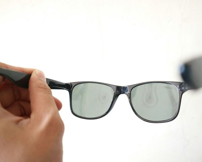 Close-up of hand holding sunglasses against white background