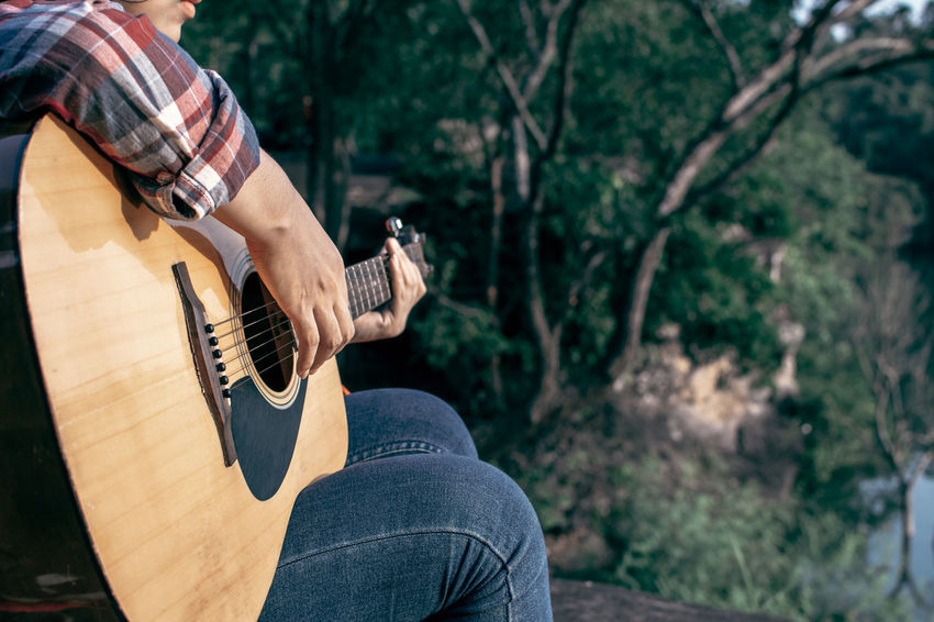 Day Guitar Jeans Lifestyles Music One Person Outdoors Playing Sitting