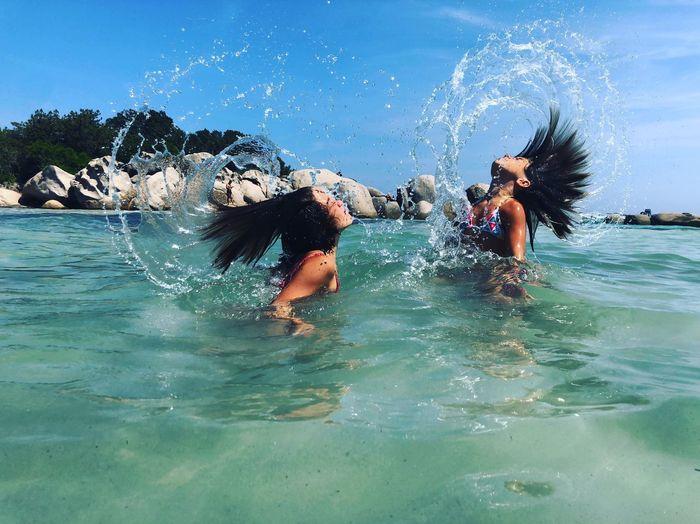 Side view of girls splashing hair while swimming in sea