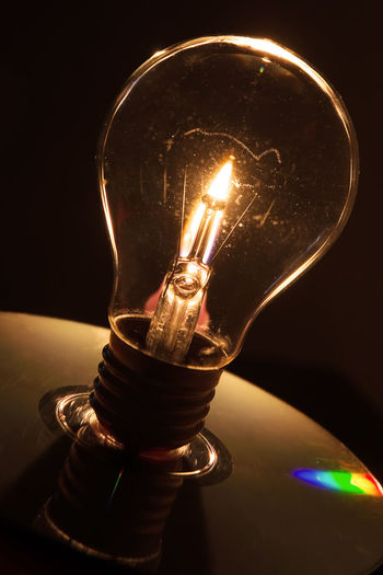 Lightbulb and candle flame Brainstorm Bulb Burn Candle Concept Dark Electric Electricity  Electricity  Energy Filament Fire Flame Glass Idea Illuminated Illumination Incandescence Lamp Light Light Bulb Light-bulb Lightbulb Lighting Equipment Tungsten