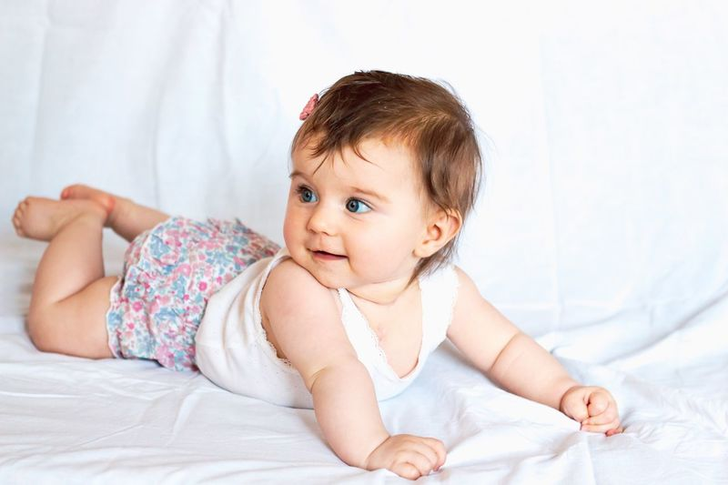 happy baby girl smiling Smiling Happy Baby Girl Fashion Lying On Front Toddler  Hair Bed Child Furniture Childhood Baby Young Bedroom Lying Down One Person Cute Innocence Babyhood Real People Full Length Front View Relaxation Linen Sheet