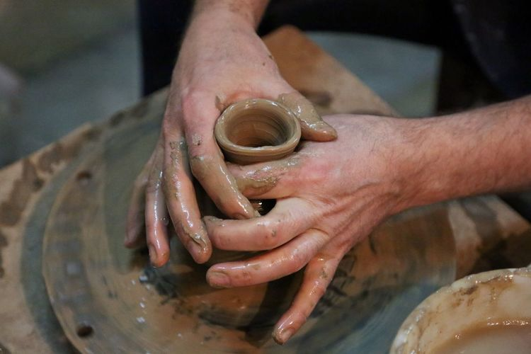 Cropped Hands Making Earthenware Pottery Wheel At Workshop