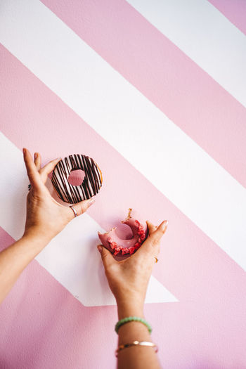 Cropped image of woman holding donuts over pink background