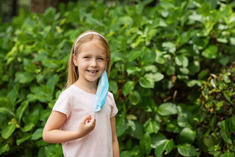 Portrait of smiling girl with mask standing against plants