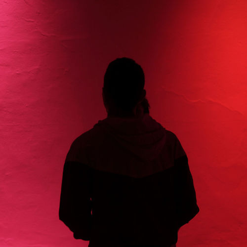 Rear view of silhouette man standing against red wall