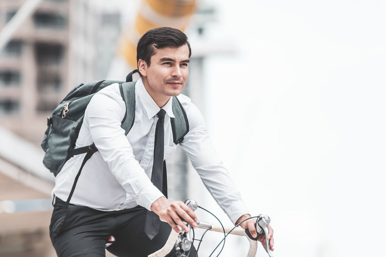 Young man with bicycle in background