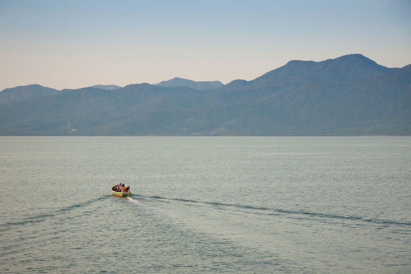 Person in boat on sea against mountain range