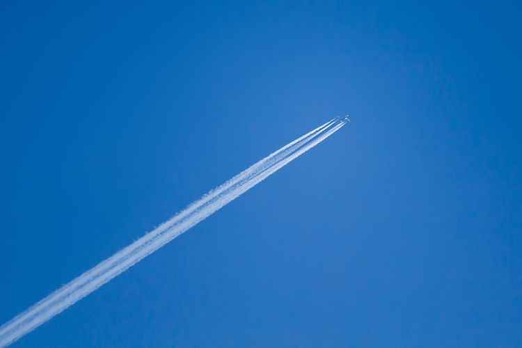 White trail from an airplane in the blue sky