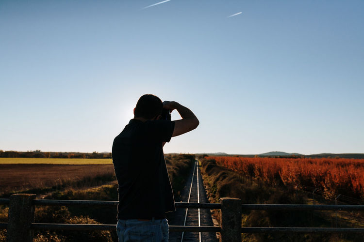 Rear view of man photographing railroad tracks from bridge against sky