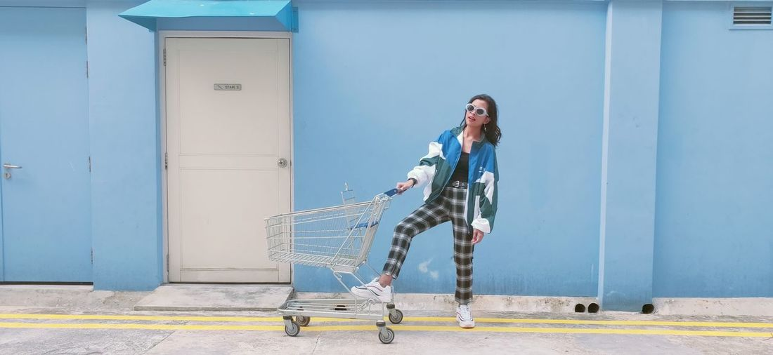 Full length of woman wearing sunglasses standing by shopping cart against blue wall