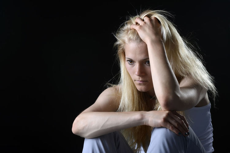 Close-up of young woman with hand in head against black background
