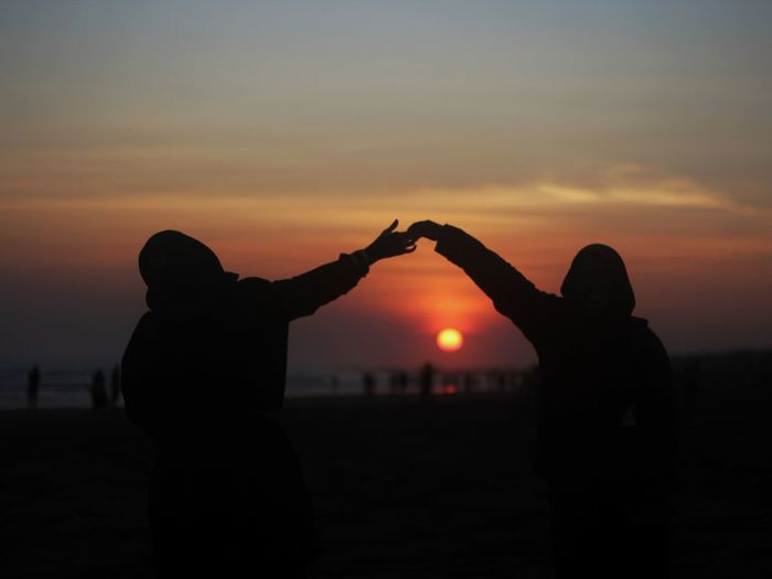 Silhouette Couple Holding Hands Against Orange Sky During Sunset