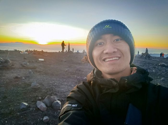 Portrait of smiling young man against sky during sunset