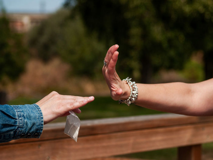 Cropped image of woman gesturing to friend giving heroin packet