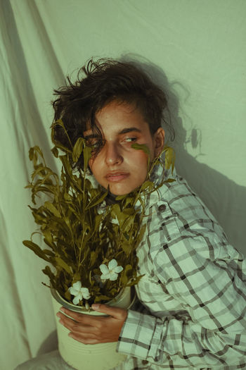 Portrait of young man with potted plant against wall