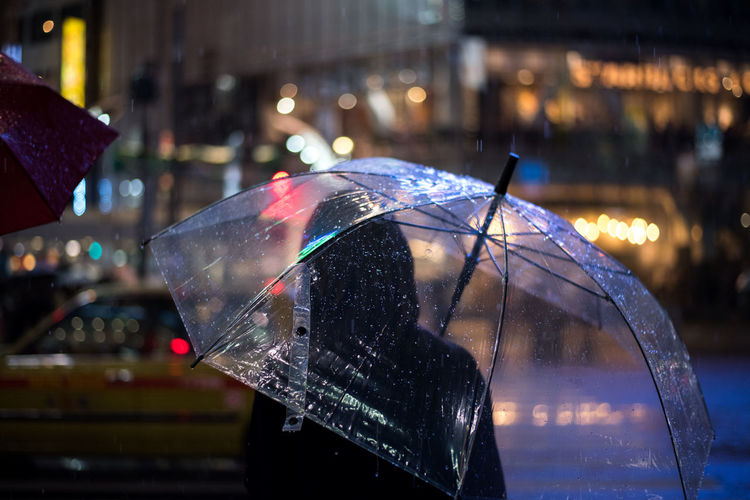 Rear view of woman carrying umbrella at night