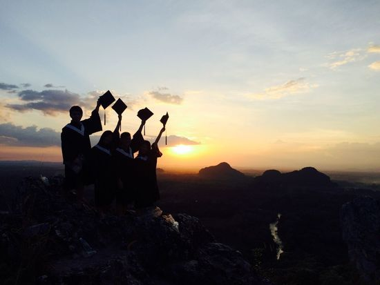 graduation photo under sunset Beauty In Nature Day Friendship Men Mountain Nature Outdoors People Real People Scenics Silhouette Sky Sunset Togetherness Women Connected By Travel