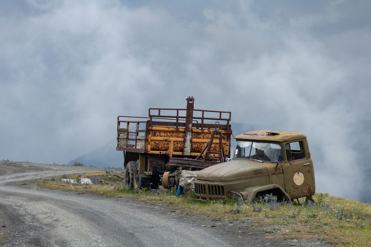 Abandoned truck on road against cloudy sky