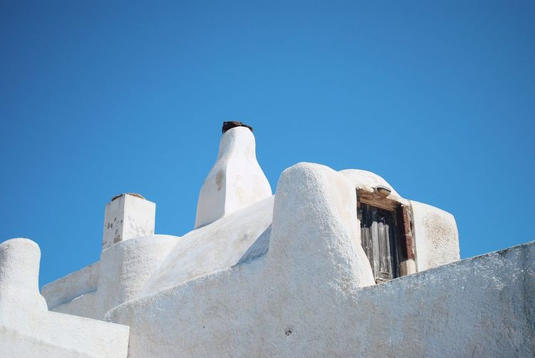Low angle view of white building against clear blue sky in oia, santorini.