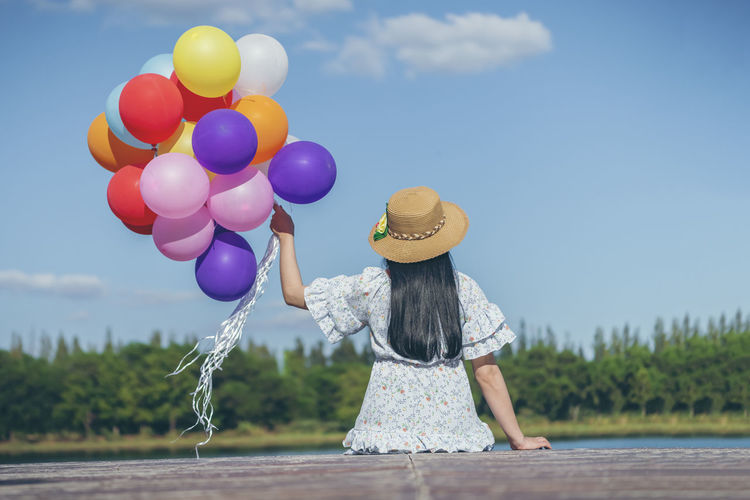 Rear view of woman with balloons standing against sky