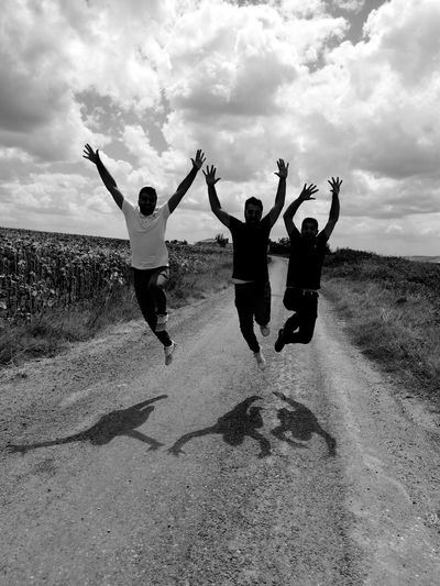 Friends jumping with arms raised against sky
