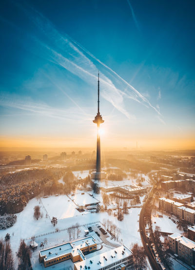 Aerial view of silhouette tower against sky in city during winter