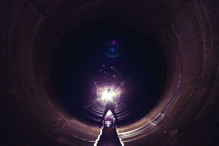 Full length of person with lighting equipment standing in sewage tunnel