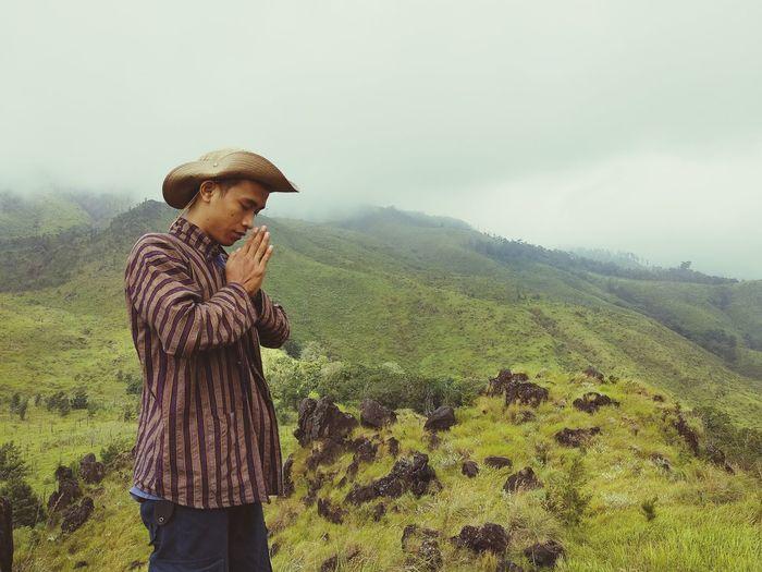 Man praying while standing on field