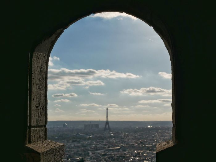 Distant view of eiffel tower seen through arch against cloudy sky