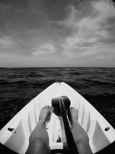Low section of woman traveling in boat sailing on sea