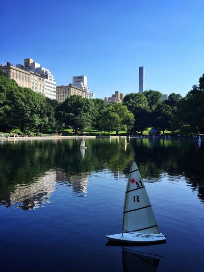 Sailboat On Pond At Central Park Against Clear Blue Sky In City