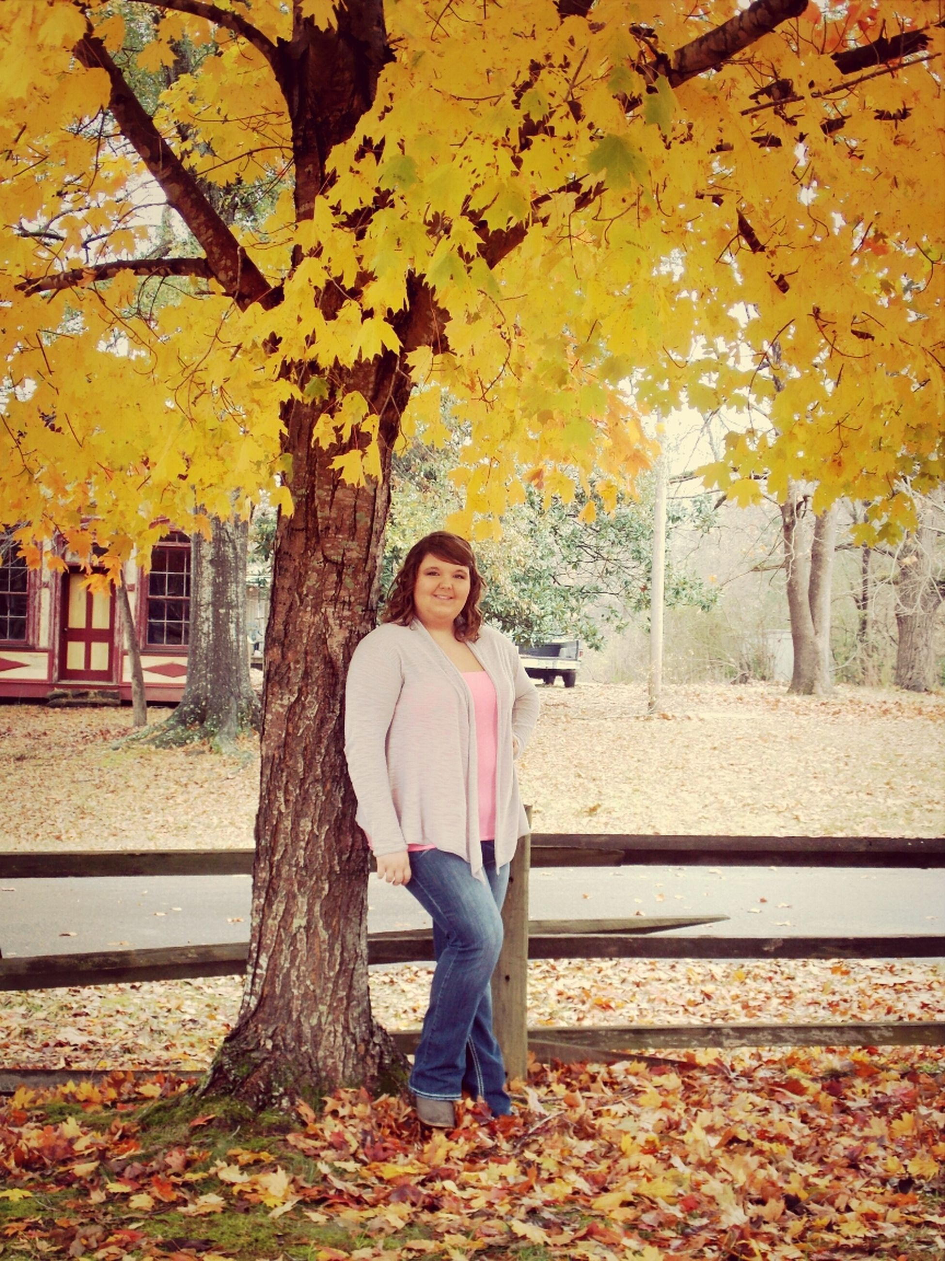 tree, person, casual clothing, lifestyles, autumn, full length, young adult, leisure activity, standing, season, young women, change, park - man made space, front view, looking at camera, leaf, long hair, smiling
