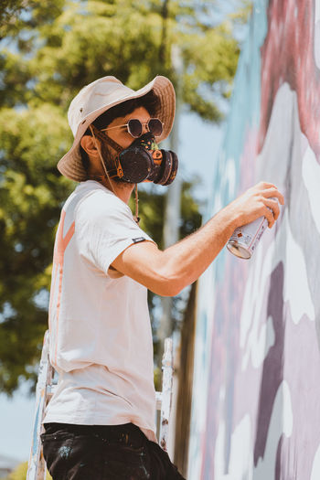 Person wearing gas mask spray painting on wall outdoors